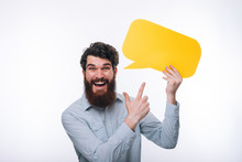 Photo Of Smiling Man In Casual Pointing At Yellow Speech Bubble