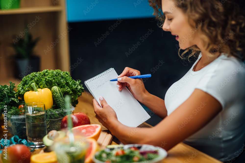 Fototapety, obrazy: Nutritionist working in office. Doctor writing diet plan on table and using vegetables. Sport trainer.