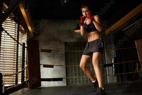 Obrazy Sztuki Walki  dramatic-full-length-portrait-of-tough-female-boxer-practicing-in-boxing-ring-copy-space