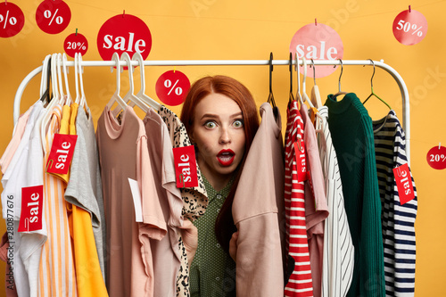 Photo surprised girl hiding among clothes on hangers woman is being surprised after hearing the prizes of clothes