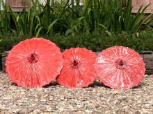 Three Red Umbrellas On Pebbled Ground