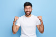 Leinwanddruck Bild - excited Arab man celebrating success with two fists in air isolated on the blue background. close up portrait, studio shot , happiness, positive emotion and feeling. I've done it. facial expression