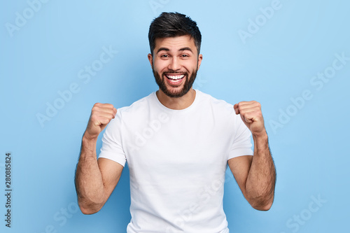 Fotografie, Obraz  excited Arab man celebrating success with two fists in air isolated on the blue background