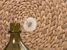 One Dandelion Flower Is Located On A Textured Background In A Green Bottle. The Flower Is Tilted. Place For Copy-paste