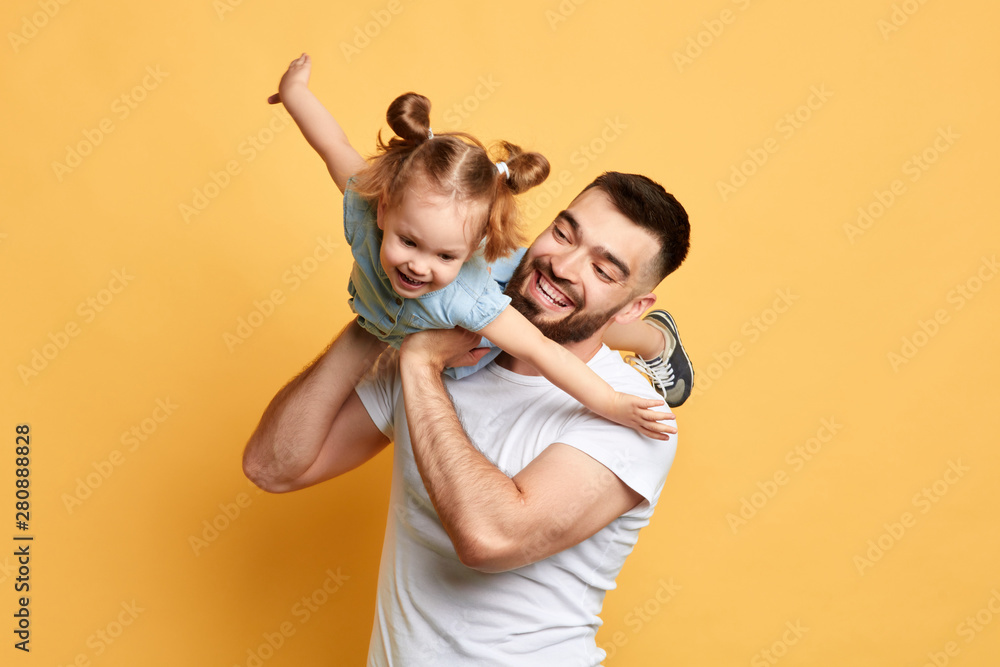 Fototapety, obrazy: cheerful happy man teaching sweet lovely daughter to fly like a plane. close up photo. isolated yellow background. studio shot, happy moments with best father