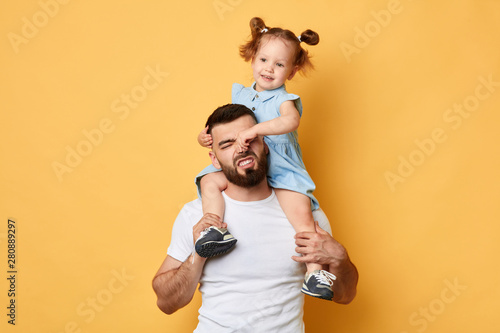 Obraz naughty girl holding her daddy's nose, display negative, angry behaviour. close up photo. isolated yellow background.father cannot manage with naughty behaviour - fototapety do salonu