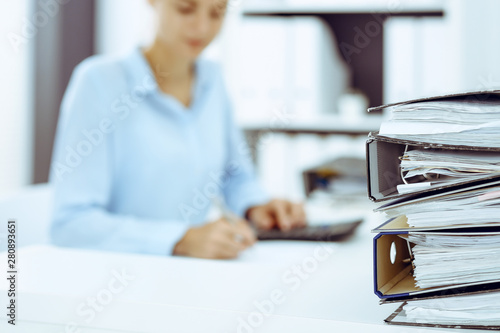 Fototapeta Binders with papers are waiting to be processed by business woman or bookkeeper back in blur. Internal Audit and tax concept obraz