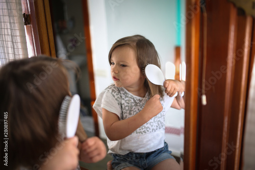 Cuadros en Lienzo funny girl child combing hair in front of mirror