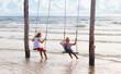 Child on swing. Kid swinging on beach.