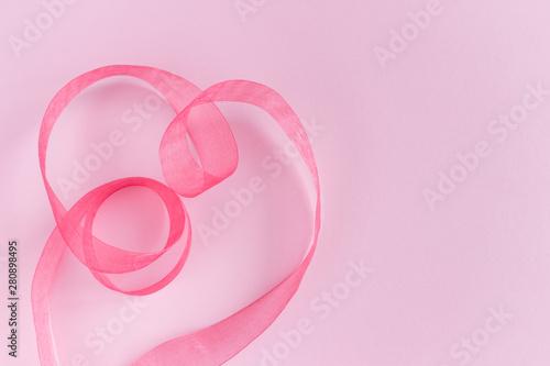 Fototapeta Festive pink satin silk ribbon waves in heart shape on pink background