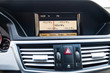 View to the interior of car with dashboard, clock, media system after cleaning before sale on parking