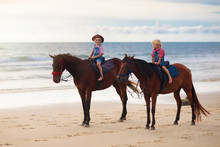 Kids Riding Horse On Beach. Children Ride Horses.