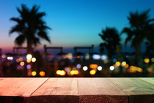 Image Of Wooden Table In Front Of Abstract Blurred Tropical Palms At Sunset Lights Background