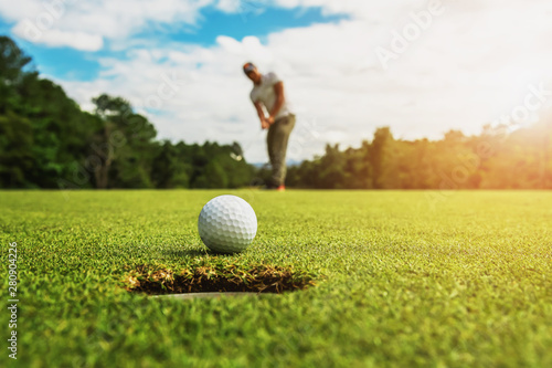 golf player putting golf ball into hole