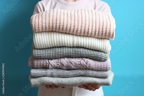 Pinturas sobre lienzo  a stack of sweaters in women's hands on a colored background