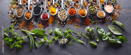 Spices and herbs in closeup on black background