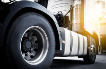 Close-up, A Big Truck Wheel, Tire Of Semi Truck Parked At Sunset Sky. Industry Freight Truck Transportation.