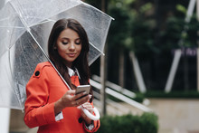 Woman Writing Sms On The Street With Umbrella. Outdoor Portrait Of Young Beautiful Woman Chating With Friends, Standing On Street.