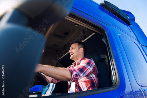 fototapeta na szkło Truck driver occupation. Professional middle aged trucker in cabin driving truck and smiling. Transportation industry.