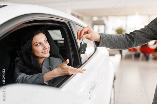 Cadres-photo bureau Pain Happy woman takes the key to new car in showroom