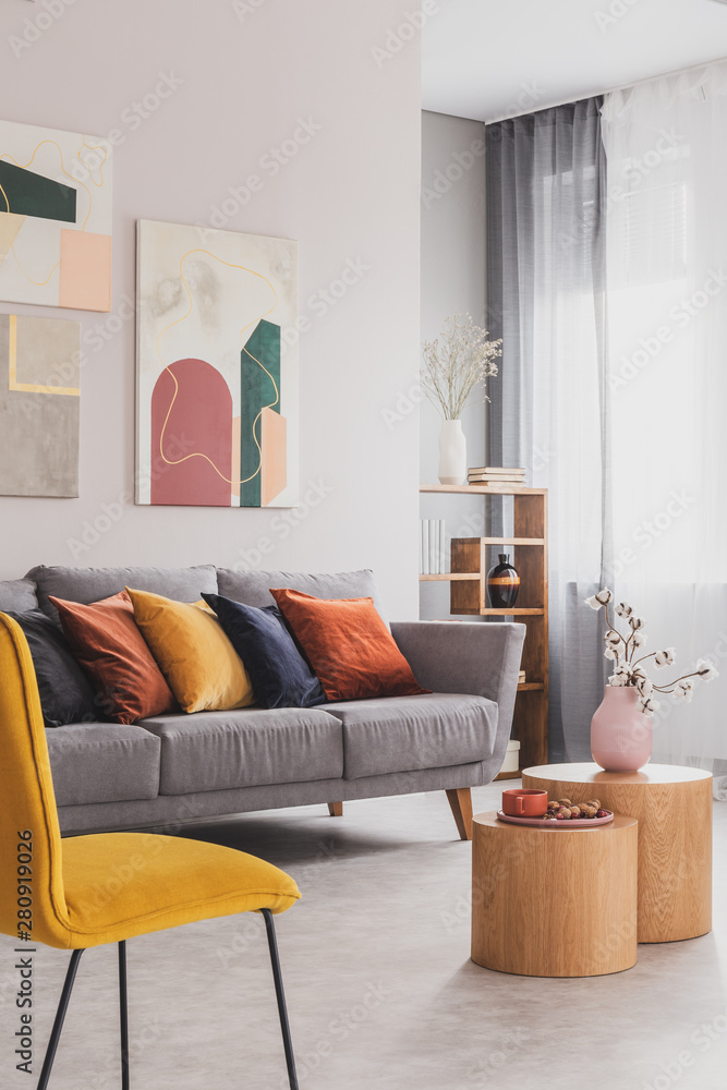 Fototapeta Yellow, orange, black and brown pillows on comfortable grey scandinavian sofa in bright living room interior with abstract paintings on the wall