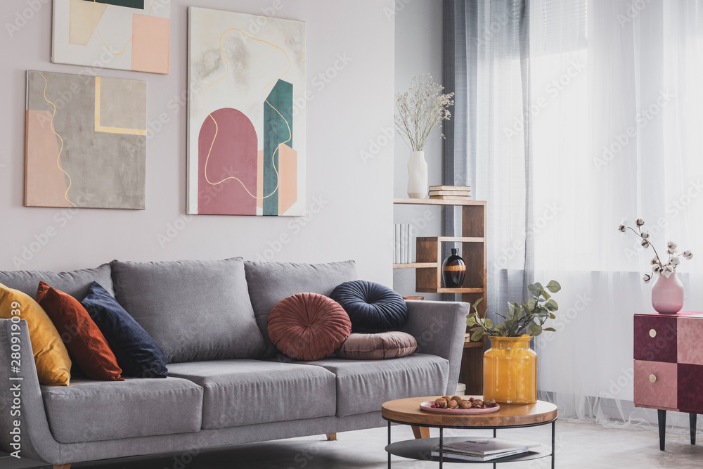 Fototapeta Coffee table in front of grey couch in scandinavian living room