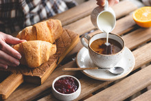 Tasty Breakfast With Croissants, Coffee With Cream And Jam. Woman's Hand Pouring Cream Into Cup Of Black Coffee