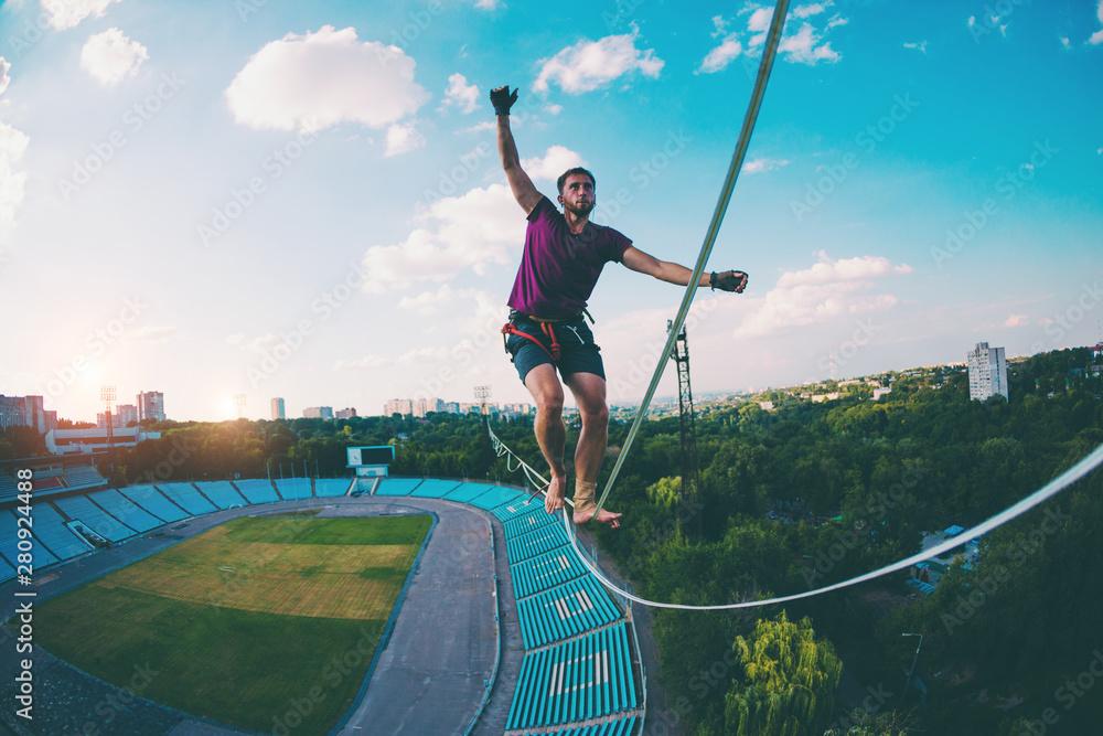 Fototapety, obrazy: Highliner goes over the stadium.