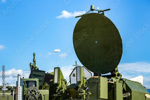 Fotografía  Military radar radio locator station, parabolic antenna on background blue sky