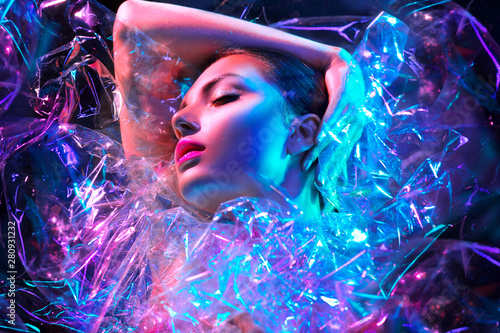 Foto op Plexiglas Beauty Fashion model woman in colorful bright neon lights posing in studio through transparent film. Portrait of beautiful sexy girl in UV. Art design colorful makeup