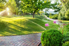 Automatic Garden Watering System With Different Sprinklers Installed Under Turf. Landscape Design With Lawn Hills And Fruit Garden Irrigated With Smart Autonomous Sprayers At Sunset Evening Time