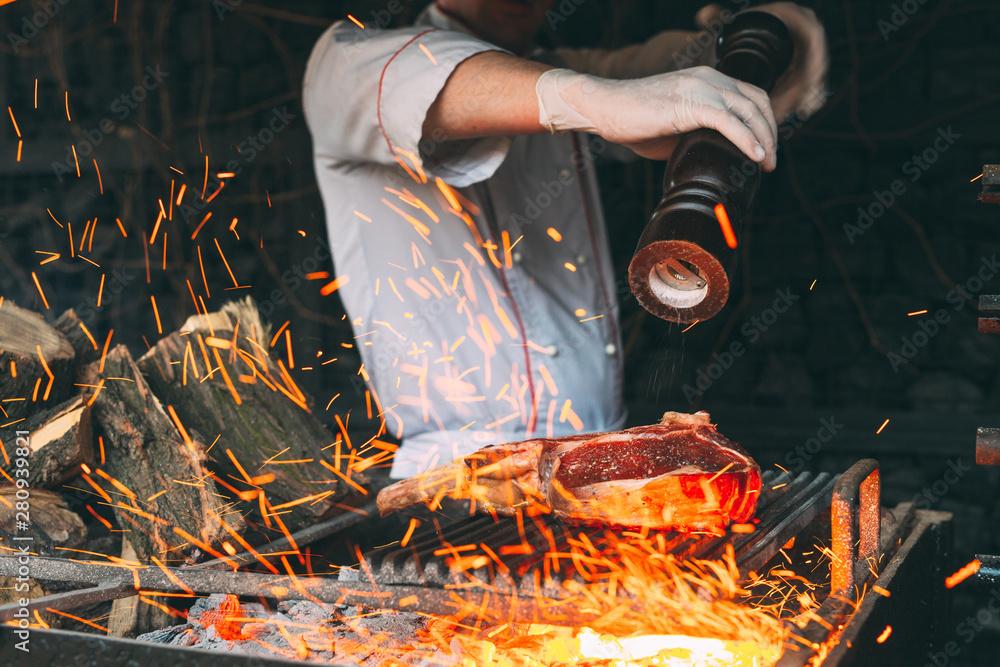 Fototapety, obrazy: Chef pepper the steak on fire.