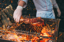 Chef Cooking Steak. Cook Turns The Meat On The Fire.