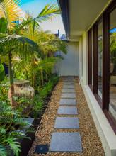 Grey Stepping Stones In Pebbles And Tropical Garden