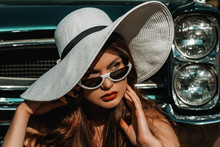 Outdoor Close Up Portrait Of Young Beautiful Elegant Woman With Red Lips Makeup, Wearing Trendy White Cat Eye Sunglasses, Wide Brim Hat, Posing Near Stylish Retro Car. Model Looking Aside