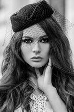 Outdoor Close Up Retro, Vintage Fashion Portrait Of Young Elegant Woman Wearing Hat With Veil Posing In Street. Model With Beautiful Long Hair.