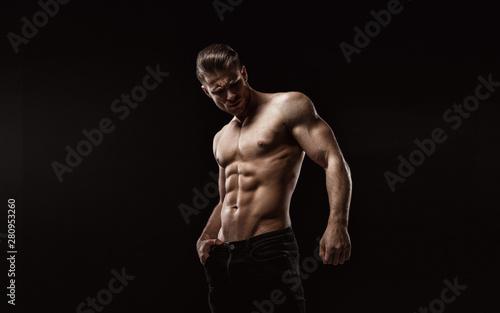 Fototapeta  Muscular model sports young man on dark background