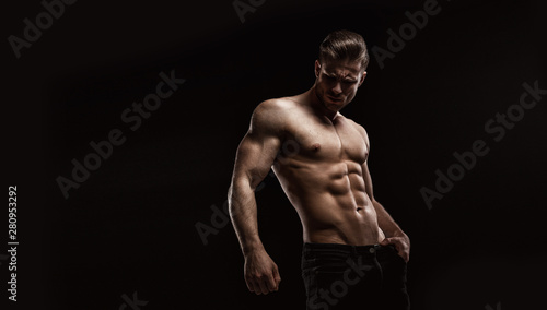 Photo Muscular model sports young man on dark background