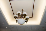 Interior design ceiling with led spot light fixtures and vintage bronze retro style lamp, white luxury designer ceiling