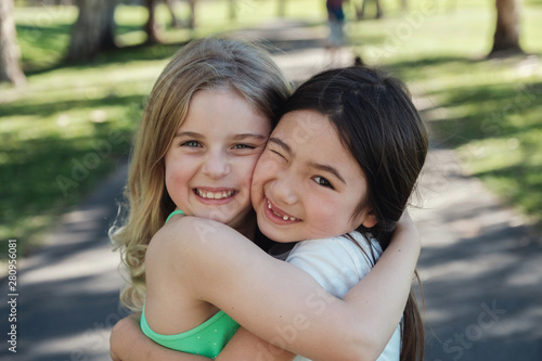 Fotografie, Obraz Happy and healthy mixed ethnic young little girls hugging and smiling in the par