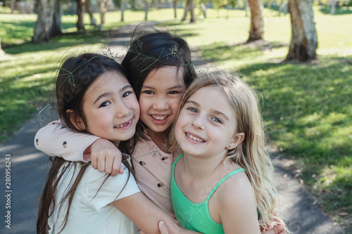 Obraz na plátně Happy and healthy mixed ethnic young little girls hugging and smiling in the par