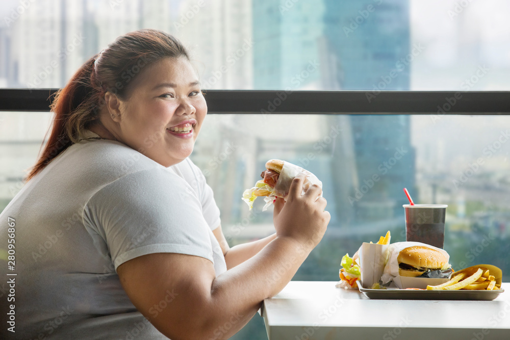Fototapeta Happy fat woman eats a hamburger in restaurant