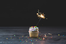 Single Cupcake With Sparkler Topped With Vanilla Icing And Colorful Confetti