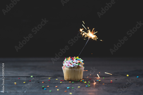 Single cupcake with sparkler topped with vanilla icing and colorful confetti Canvas Print