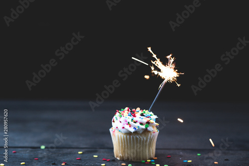 Photo  Up Close single cupcake with white icing and a sparkler