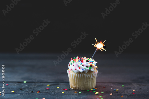 Close up vanilla cupcake with white icing and a small sparkler Canvas Print