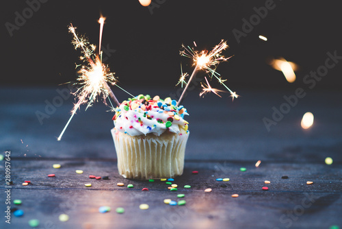 Cupcake with two sparklers and topped with vanilla icing and confetti sprinkles Canvas Print
