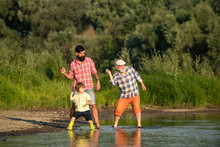 Family Game Of Stone Skipping. Three Generation Family. Father, Son And Grandfather Relaxing Together.