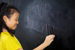 Sad little girl writing a text of stop bullying