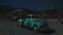 An Old Vintage USA Pickup Truck Standing In The Desert Of Nevada. The Stars Are Moving Along The Sky.